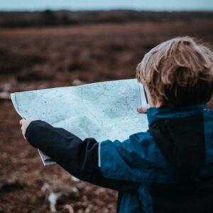 Zdjęcie dziecka z mapą pośród pola.