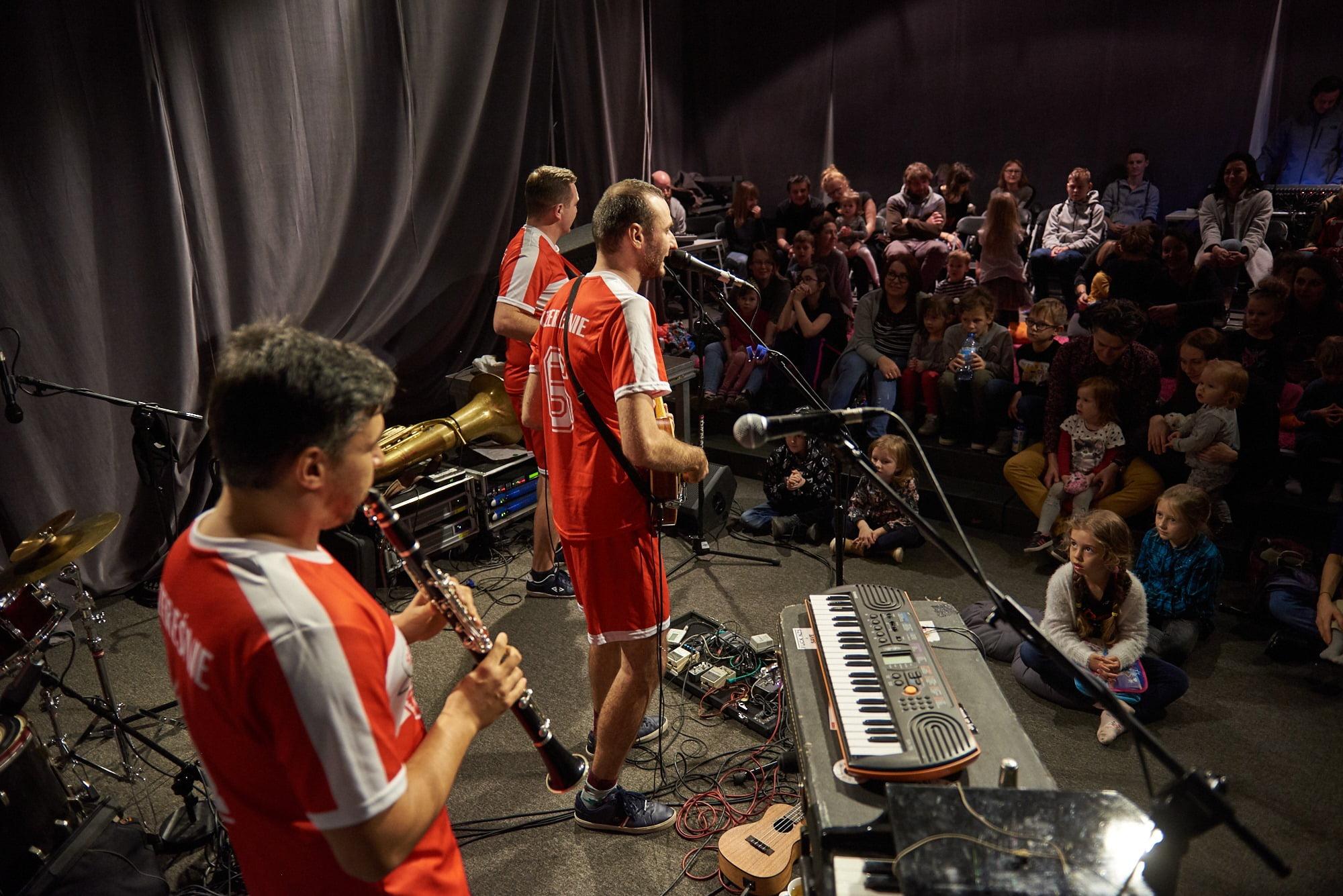 Zdjęcie trzech mężczyzn grających na instrumentach. W tle grupa dzieci i dorosłych.