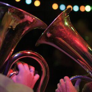 kadr od tyłu, członkowie orkiestry dętęj z tubami