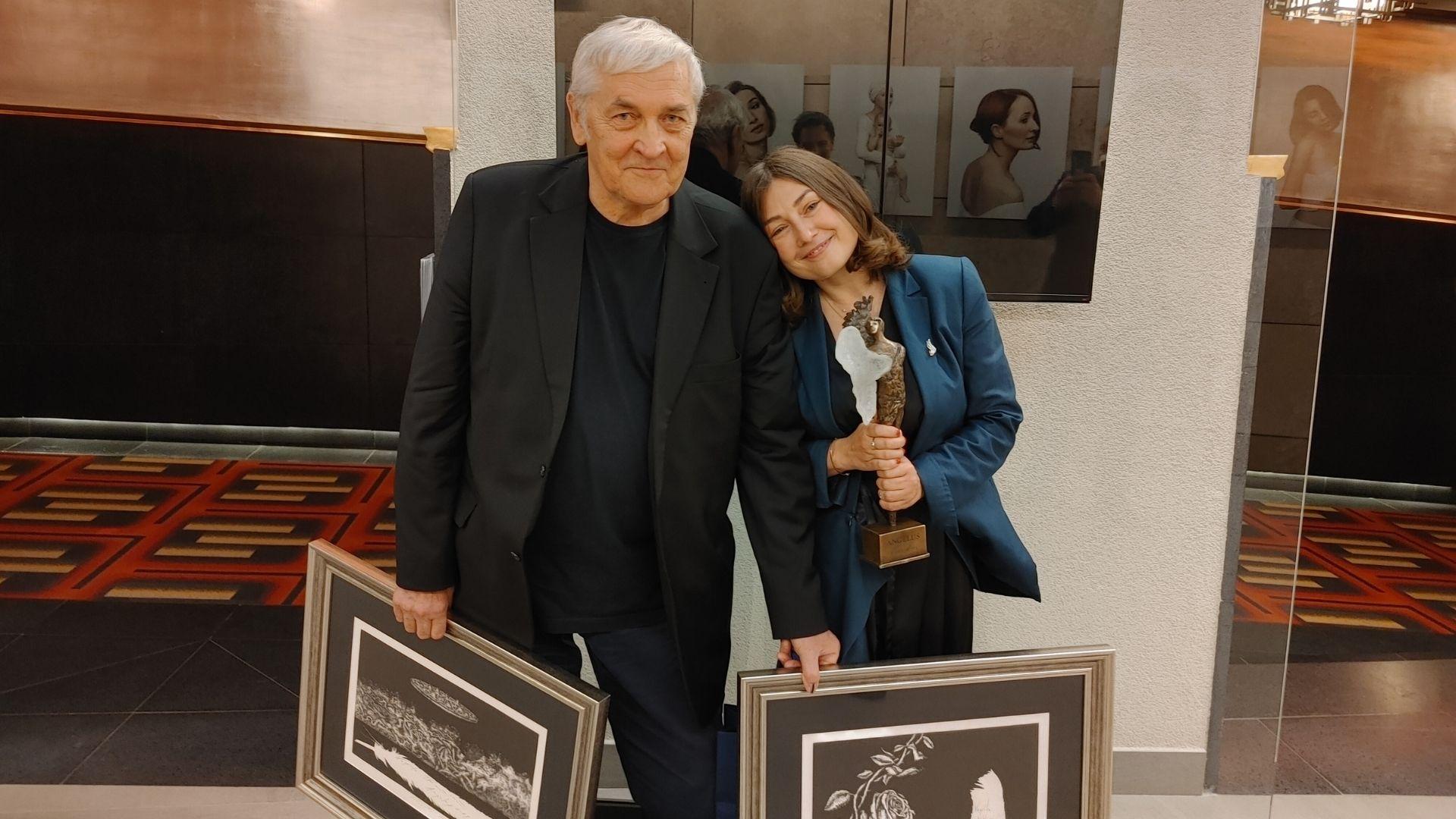 Zdjęcie przedstawia kobietę i mężczyznę z obrazami oraz statuetką.