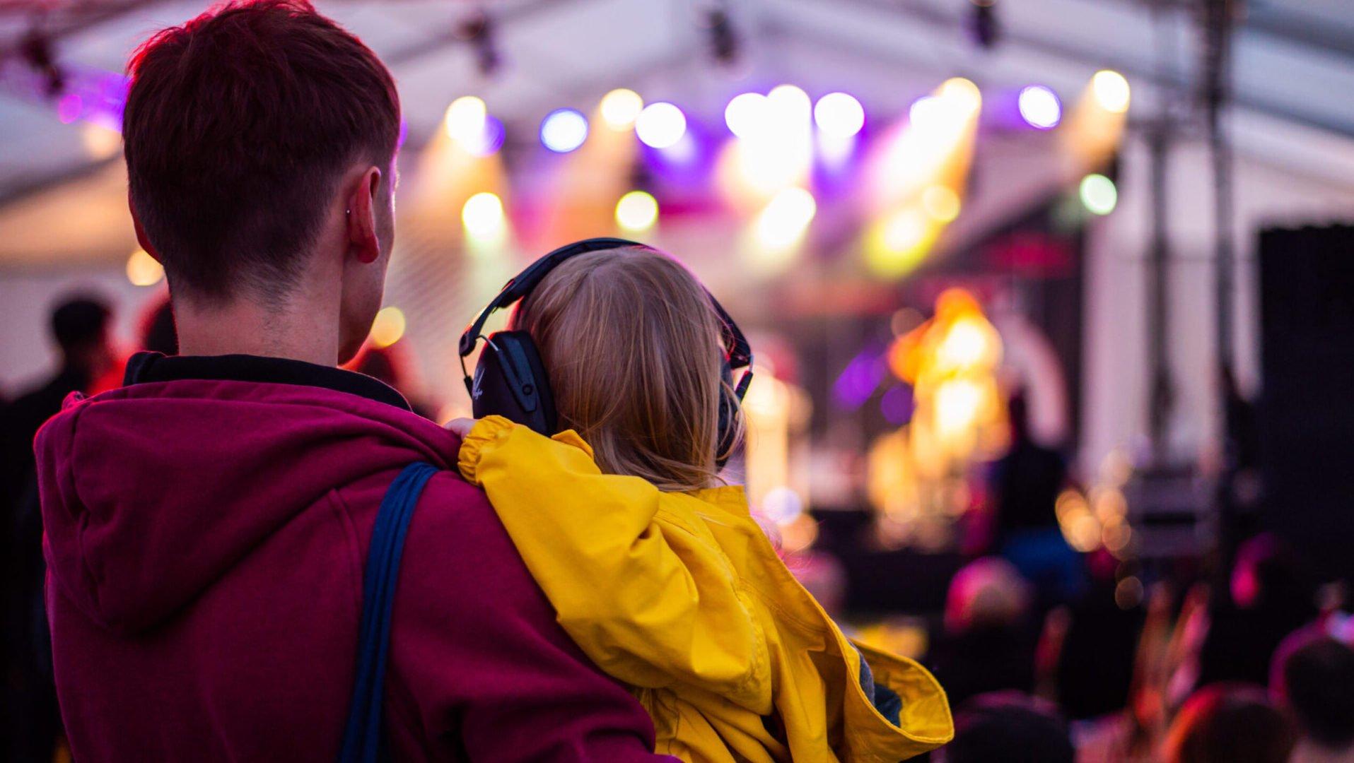 Zdjęcie mężczyzny w czerwonej bluzie oraz dziecka na jego rękach w żółtej kurtce oraz słuchawek ochronnych na głowie. W tle koncert.