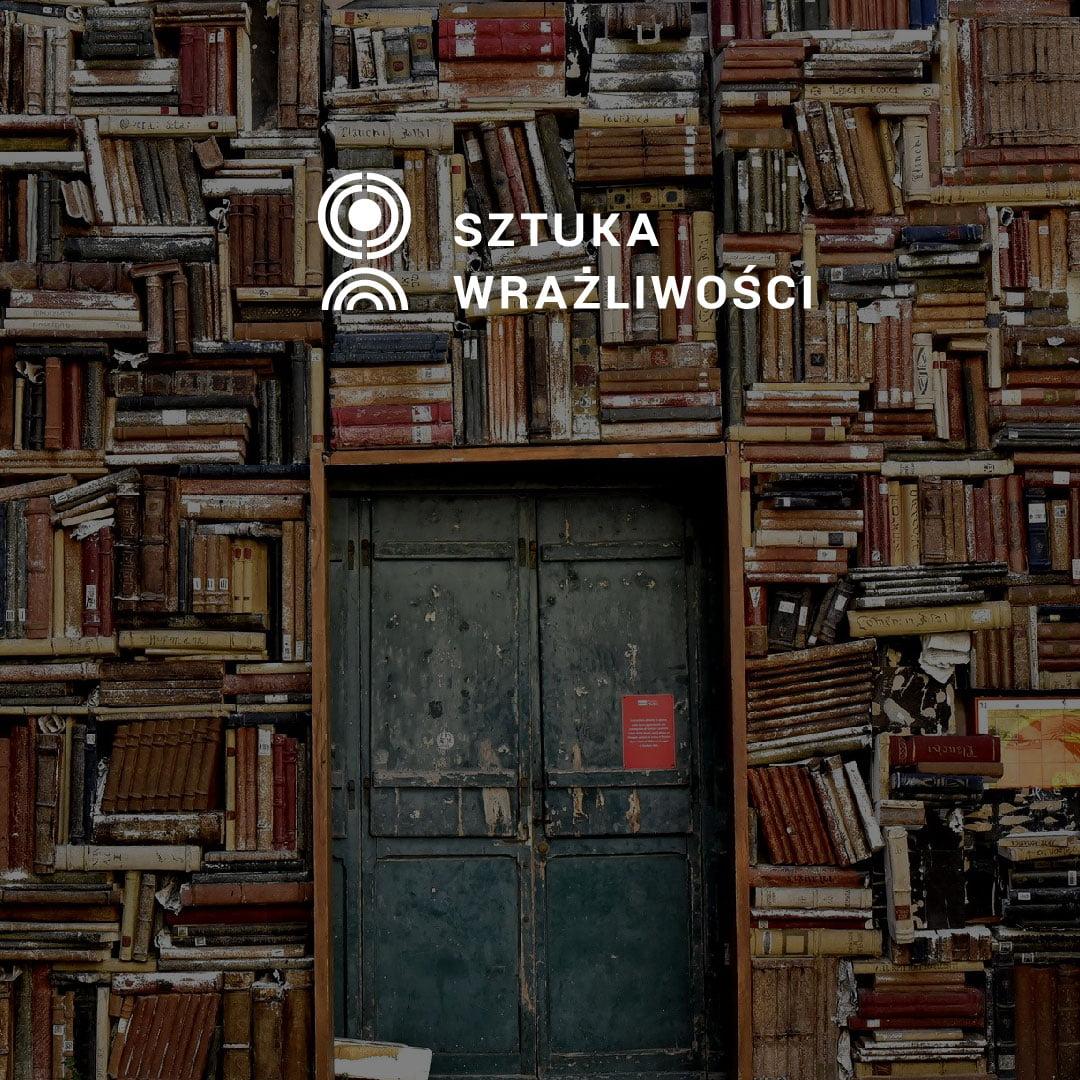 Ściana z książek i drzwi. U gór logo Sztuka Wrażliwości.