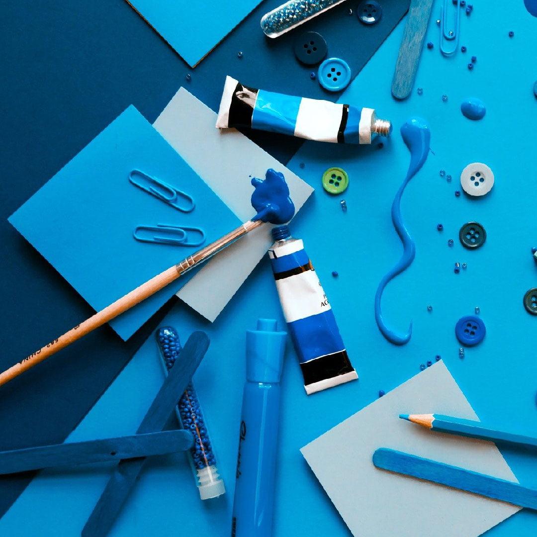 Niebieska farba, papier, kredki, spinacze - niebieskie artykuły biurowe i artystyczne.