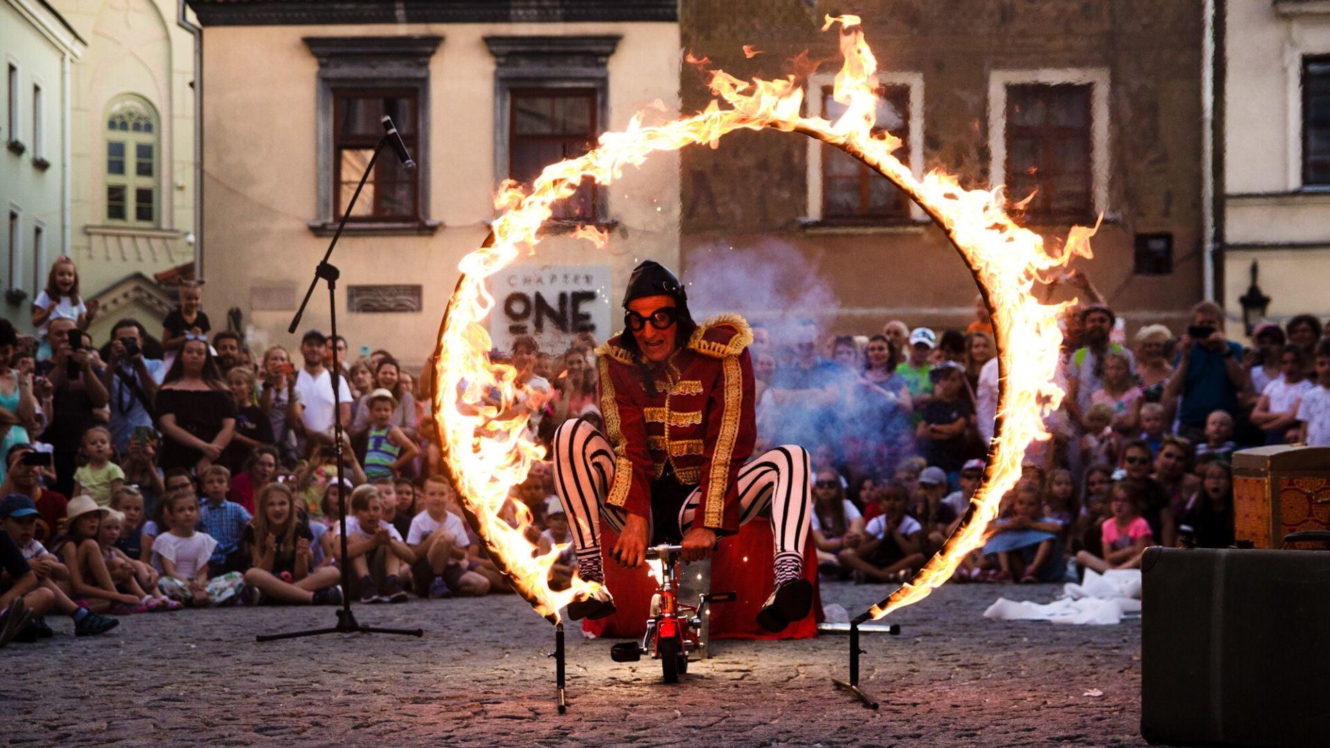 Występ artysty ulicznego podczas Carnavalu Sztukmistrzów. Mężczyzna przejeżdża na miniaturowym rowerku przez płonącą obręcz