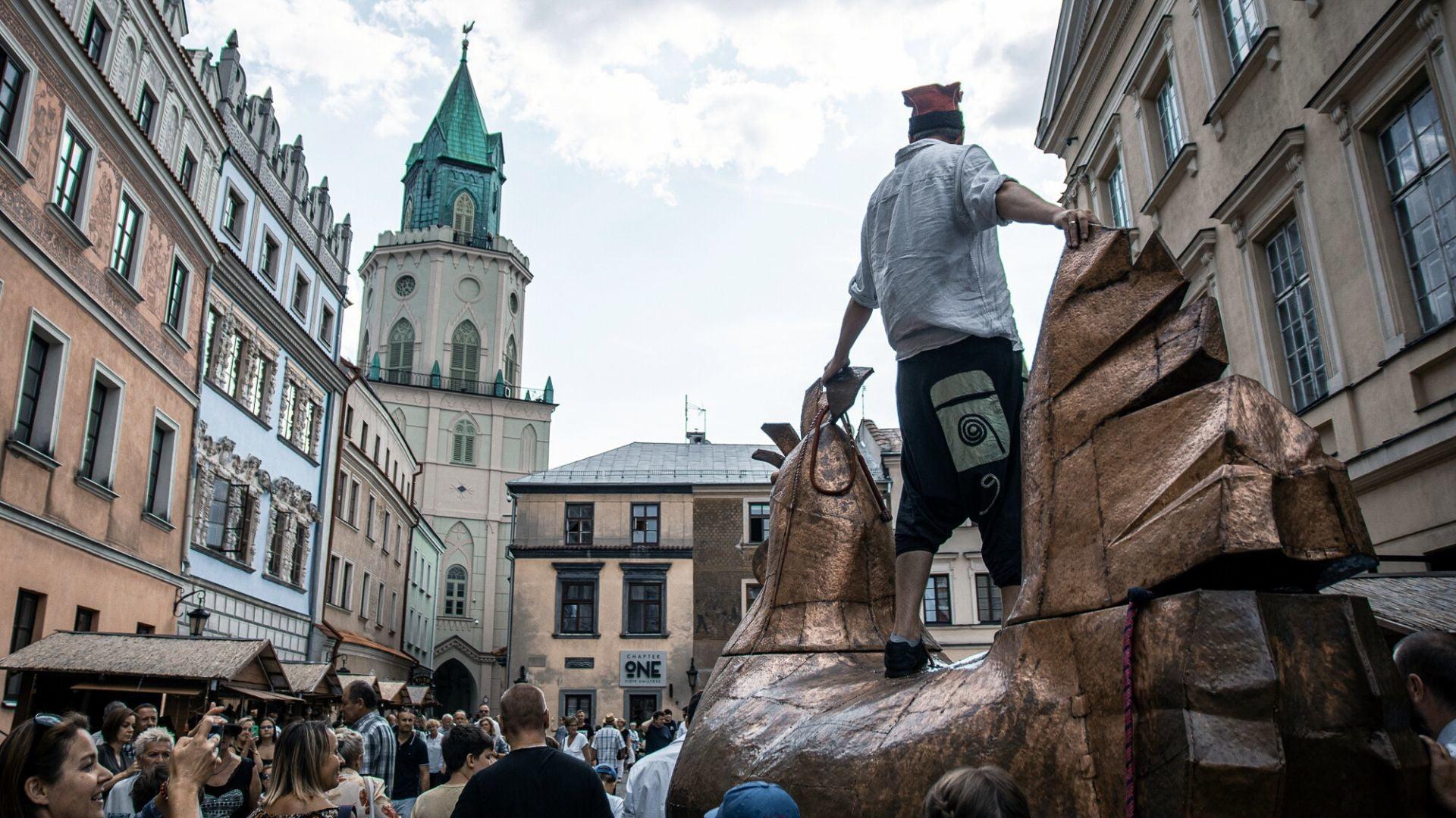 Jarmark Jagielloński. Pomiędzy tłumem spacerujących ludzi przejeżdża olbrzymia miedziana kura, na której grzbiecie stoi mężczyzna